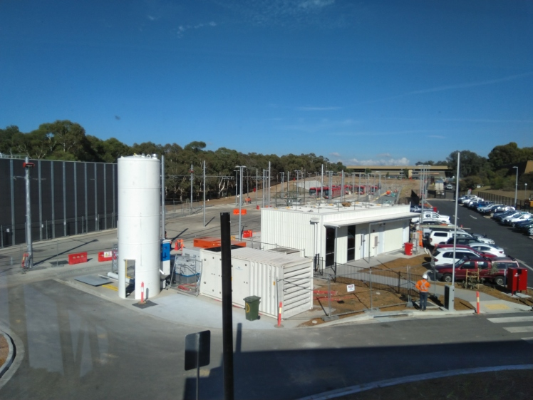 That large cylinder is a sand tower. Sand is used in the braking system to enhance friction between steel wheels and steel tracks, in an emergency. The building next to the carpark is the backup control centre. In the background the railyard, that houses the 14 light rail vehicles in our current fleet.